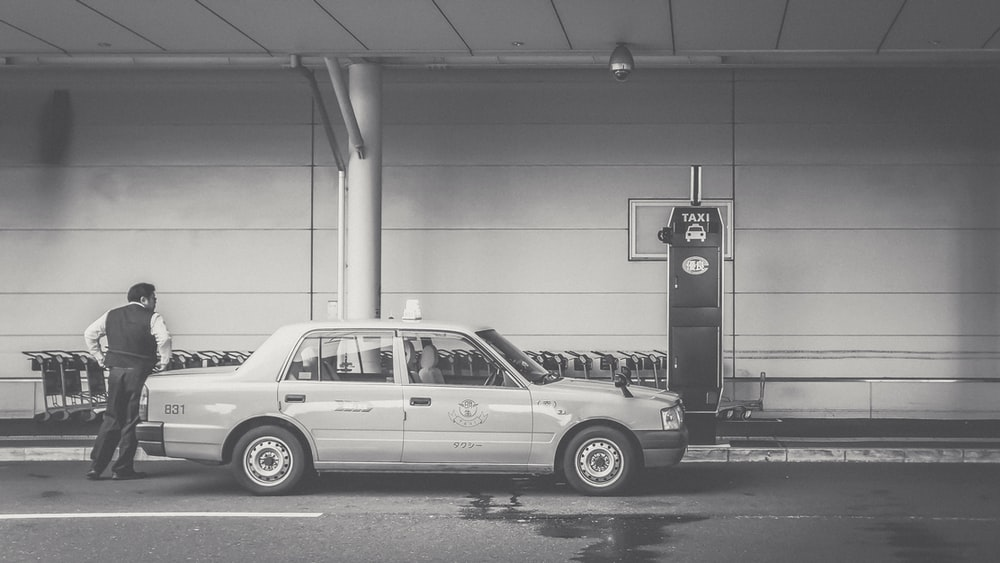 grayscale photo of man beside car
