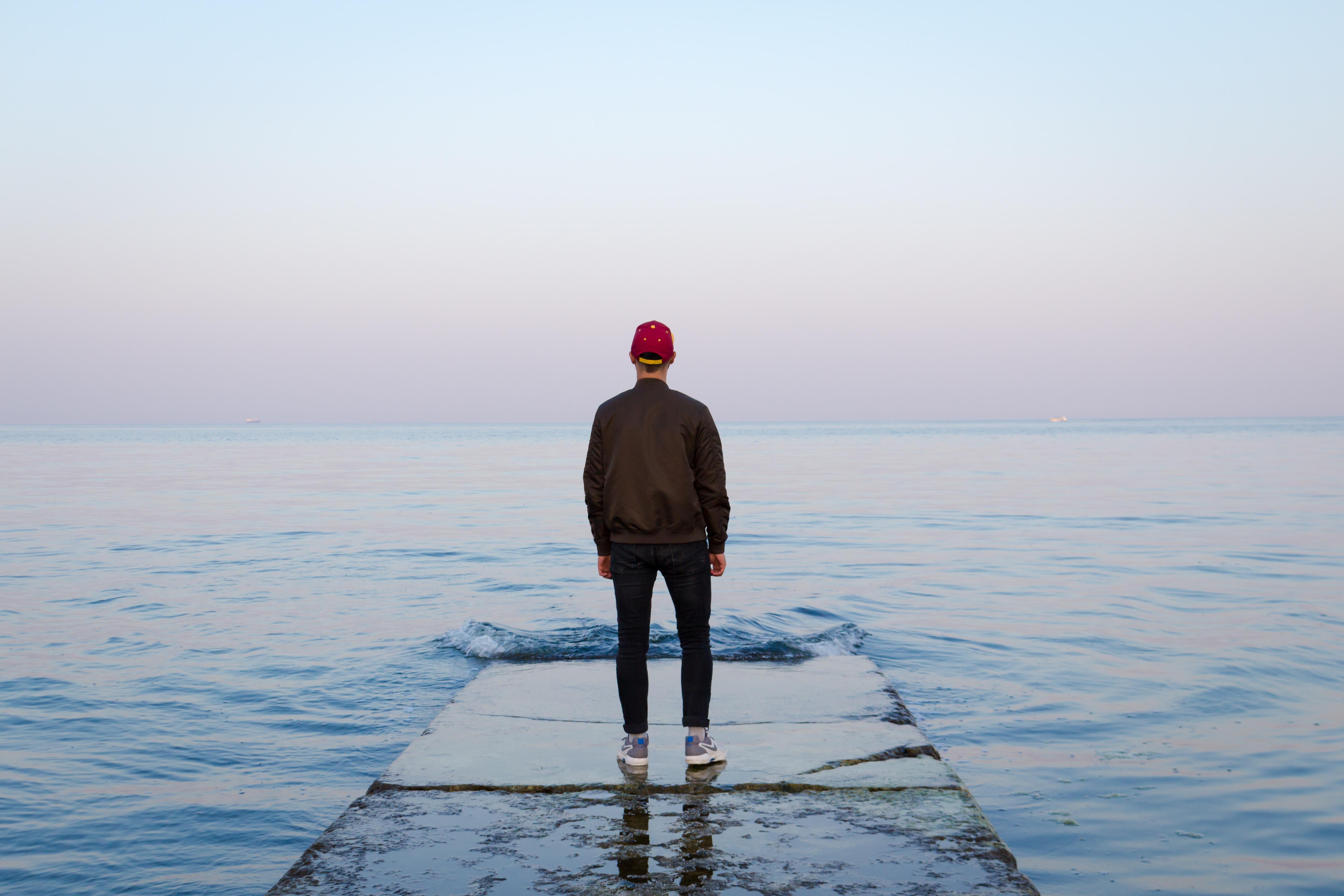 man standing on concrete dock facing sea