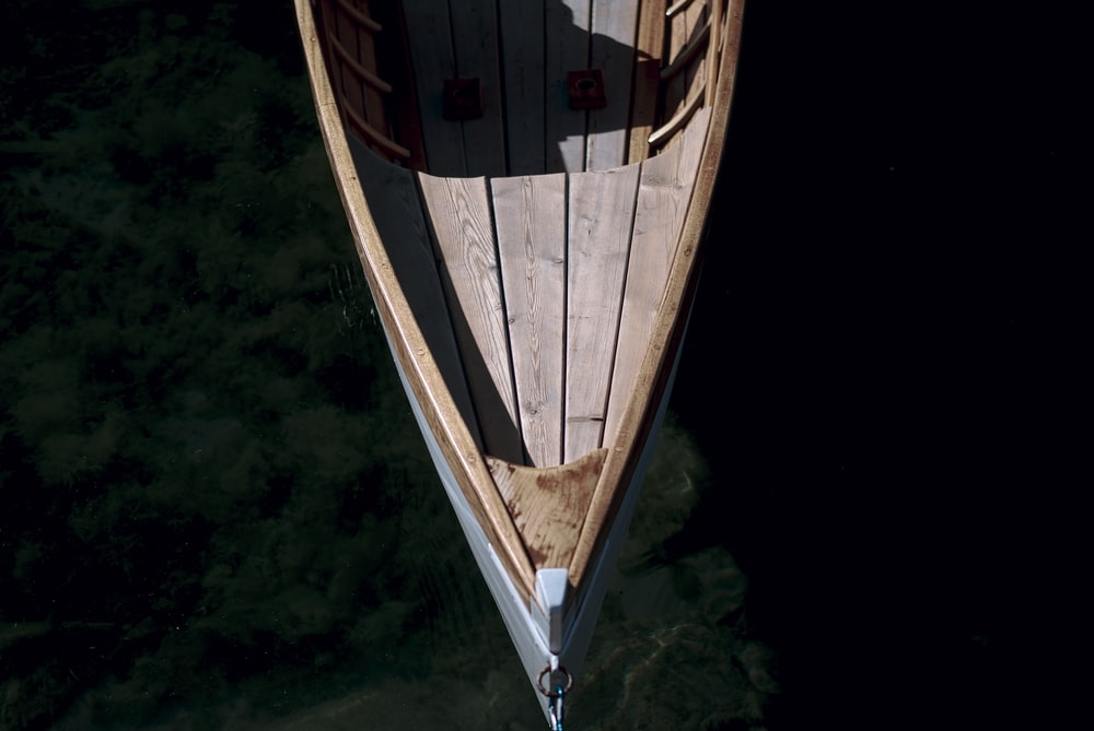 brown and white wooden boat on body of water during daytime