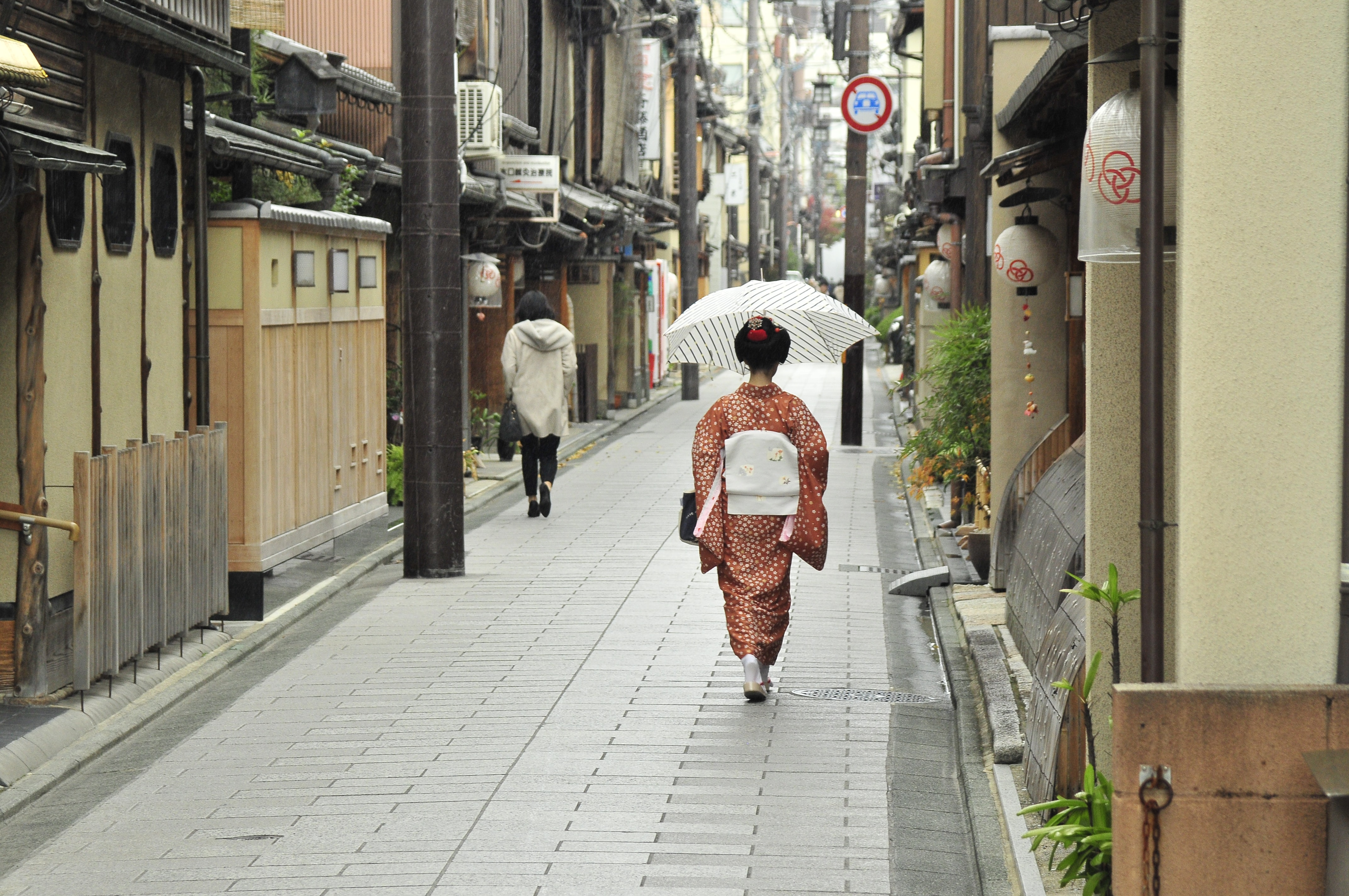 woman in Japanese traditional dress walking between houses