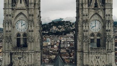 close-up photography of gray concrete clock towers ecuador teams background