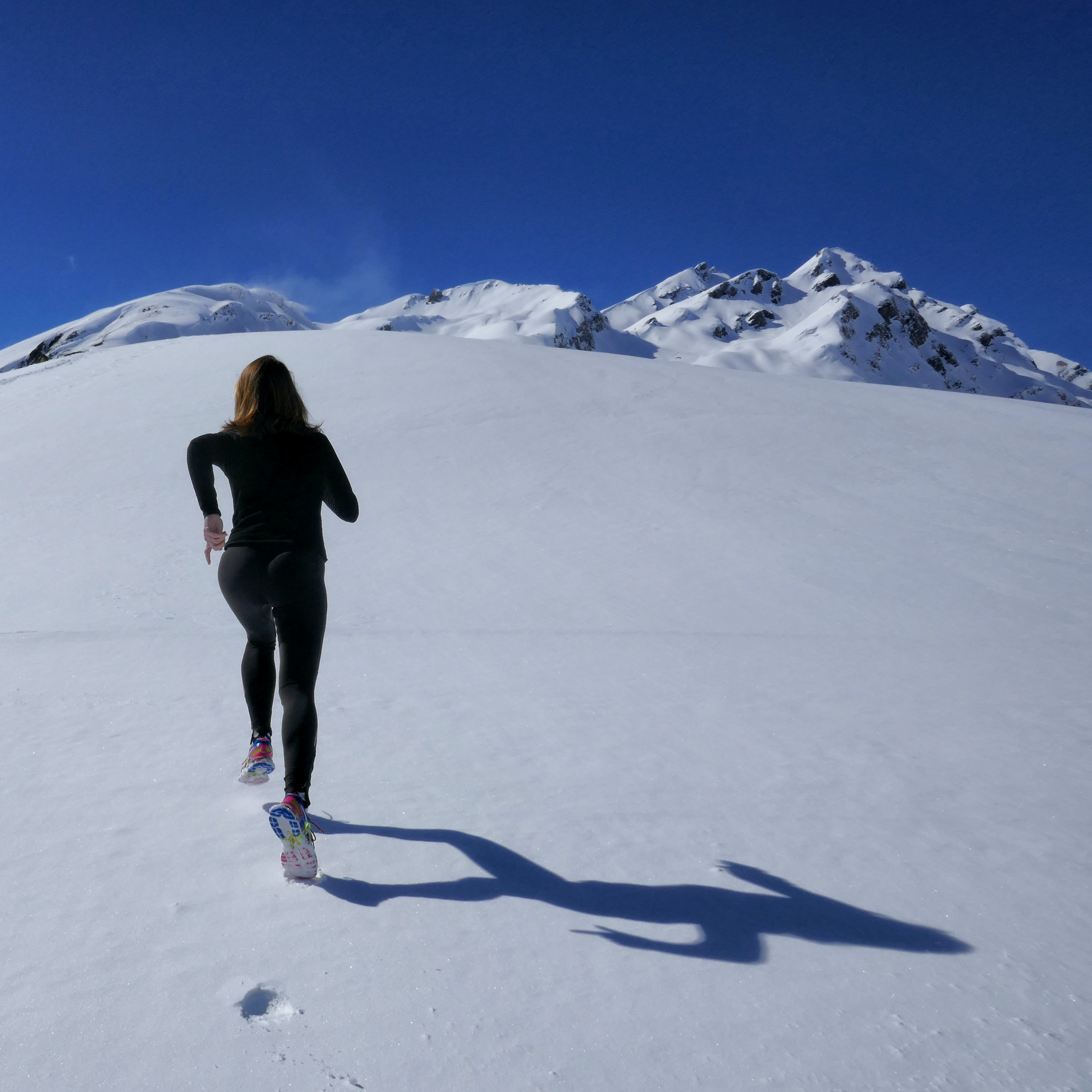 woman running on snow covered mountain