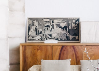 brown wooden sideboard beside beige fabric sofa