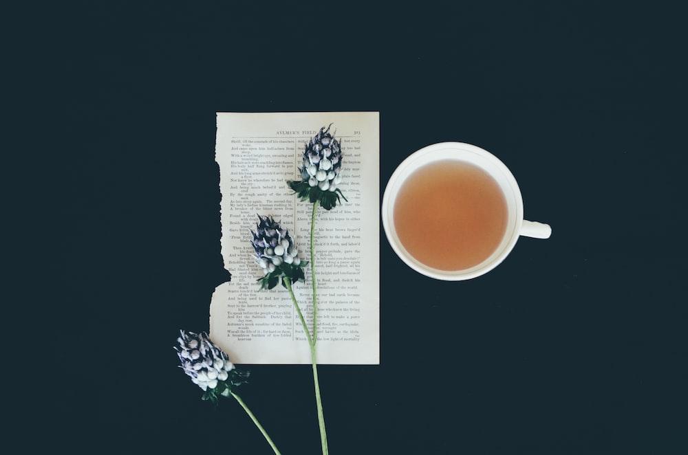 white ceramic tea cup beside white flowers