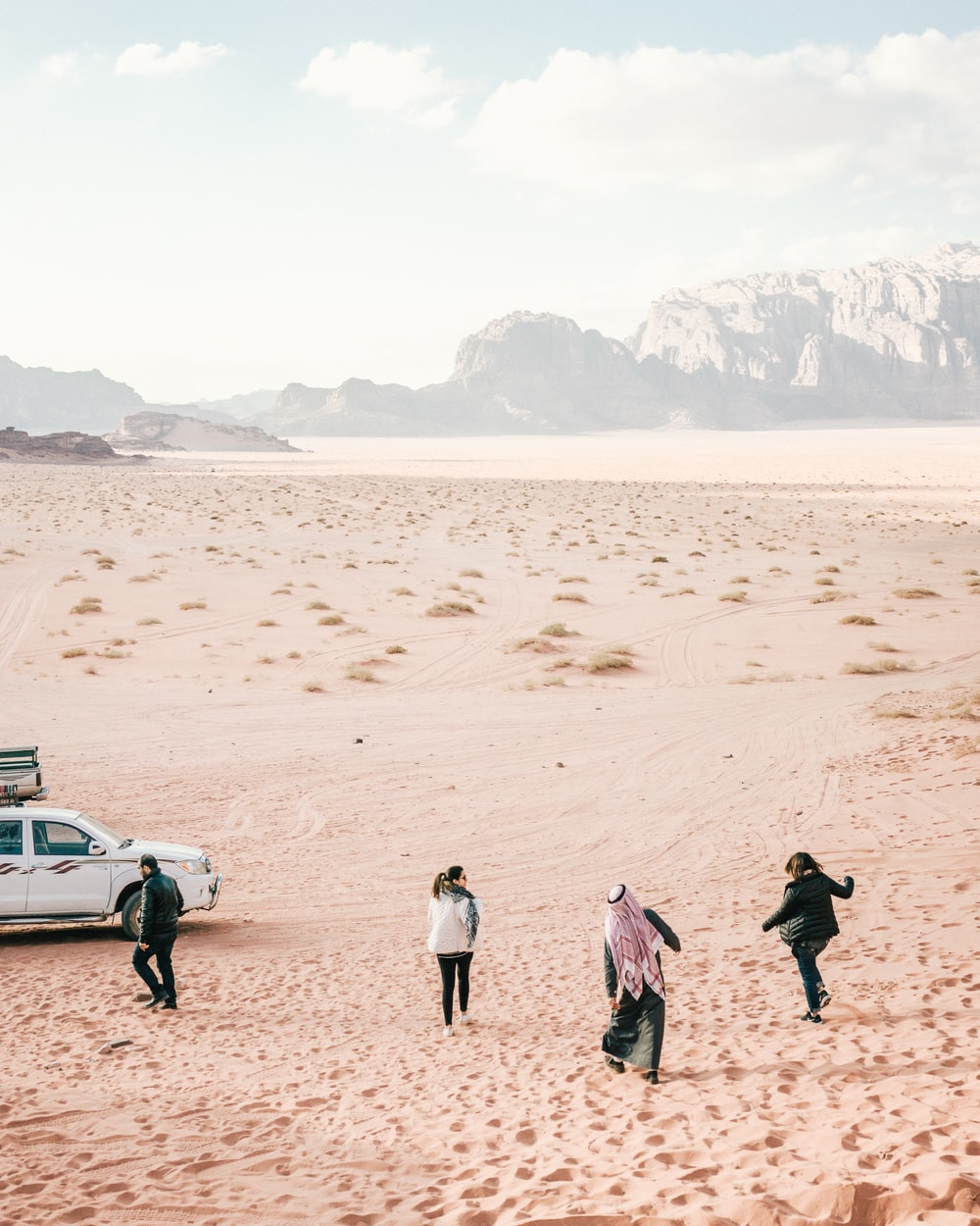 four person standing on desert