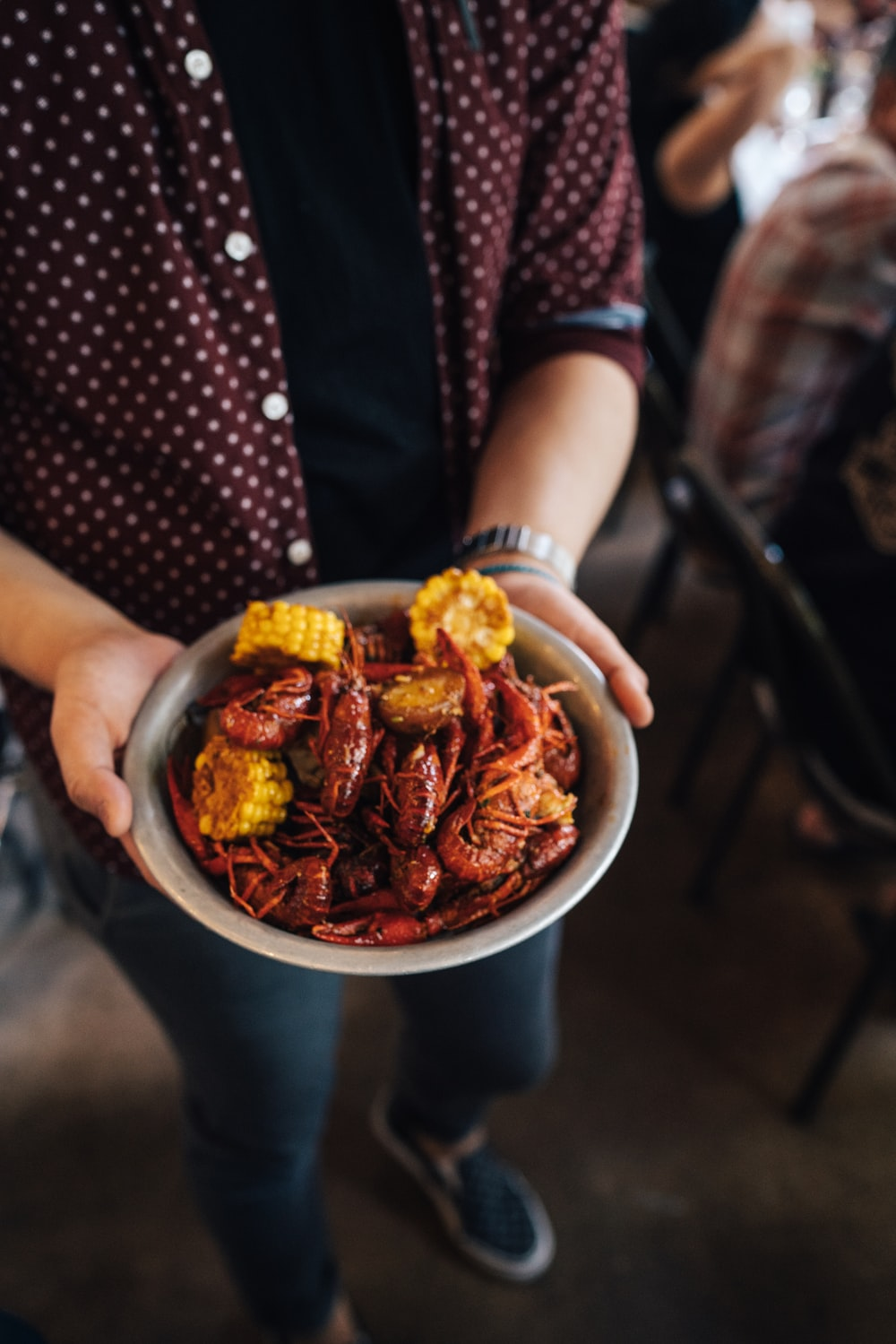person holding bowl of shrimp with slice of corn dish