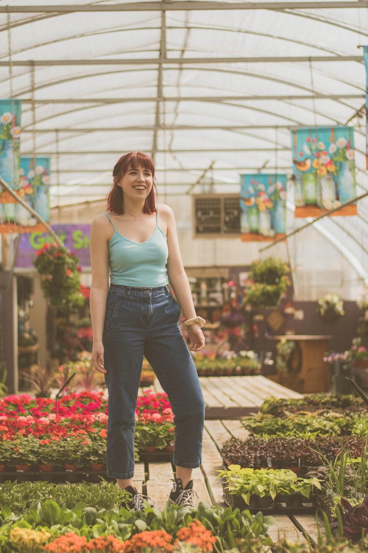woman standing near flower pots inside greenhouse