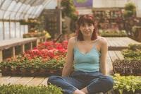 woman sitting inside green house beside plants