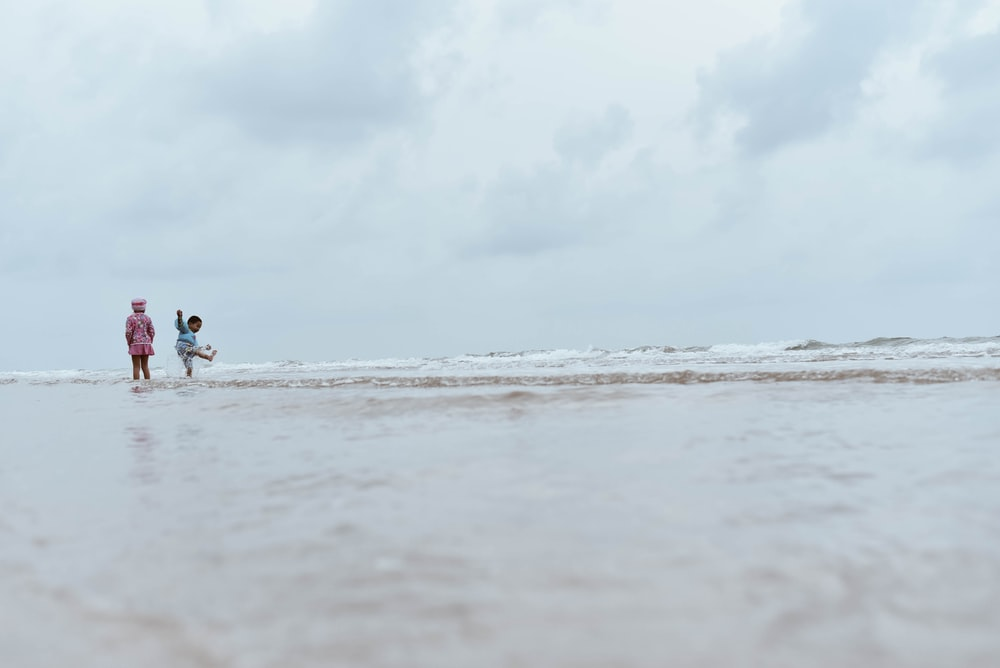 two children on beach shore