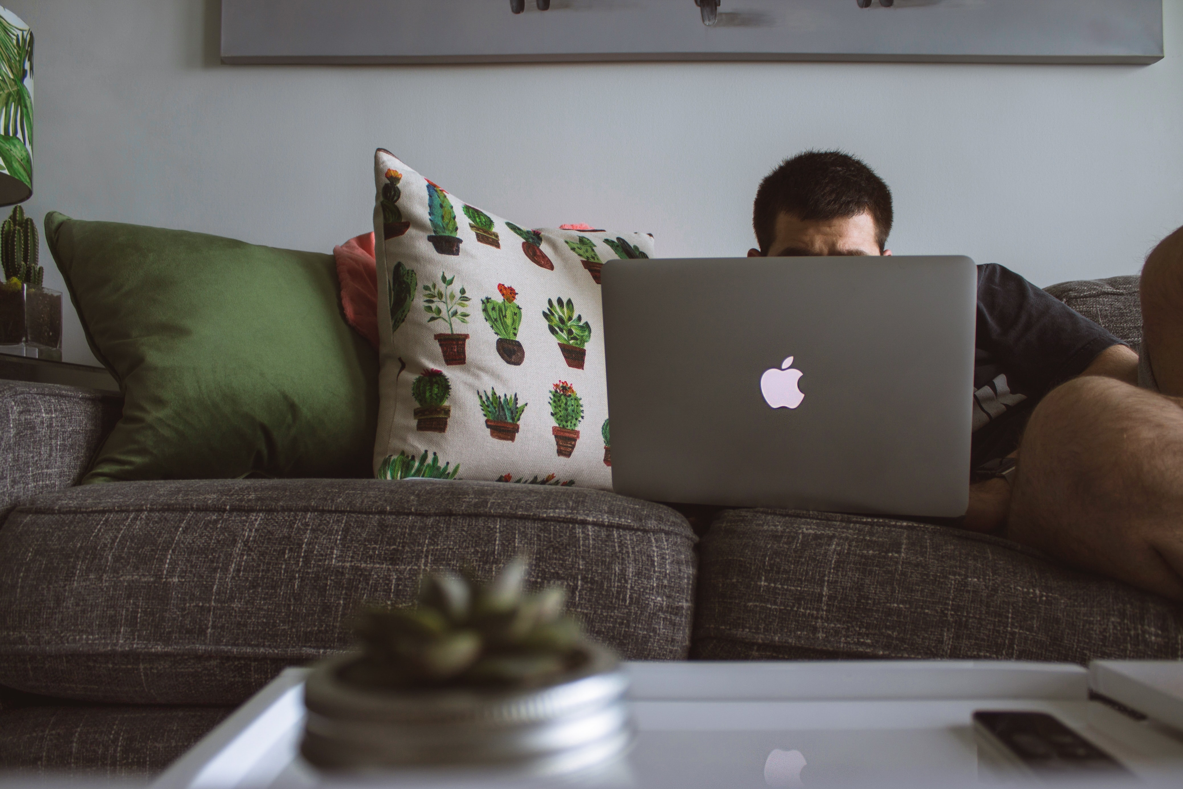 man using MacBook sat on sofa