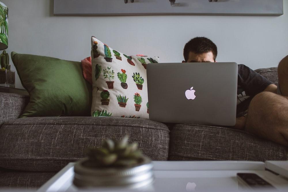 man using MacBook sat on sofa
