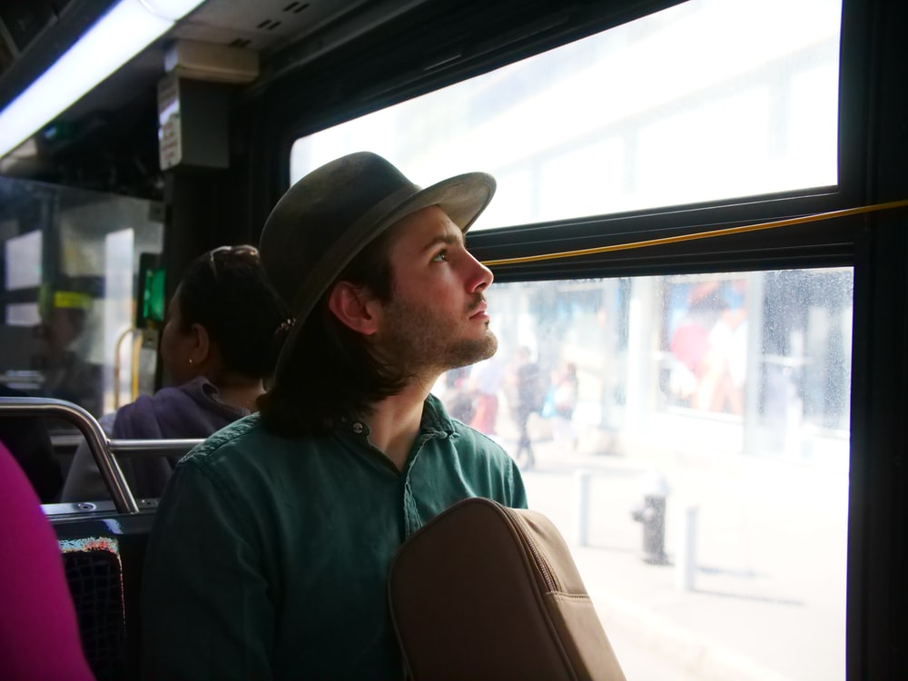 man staring outside of bus window