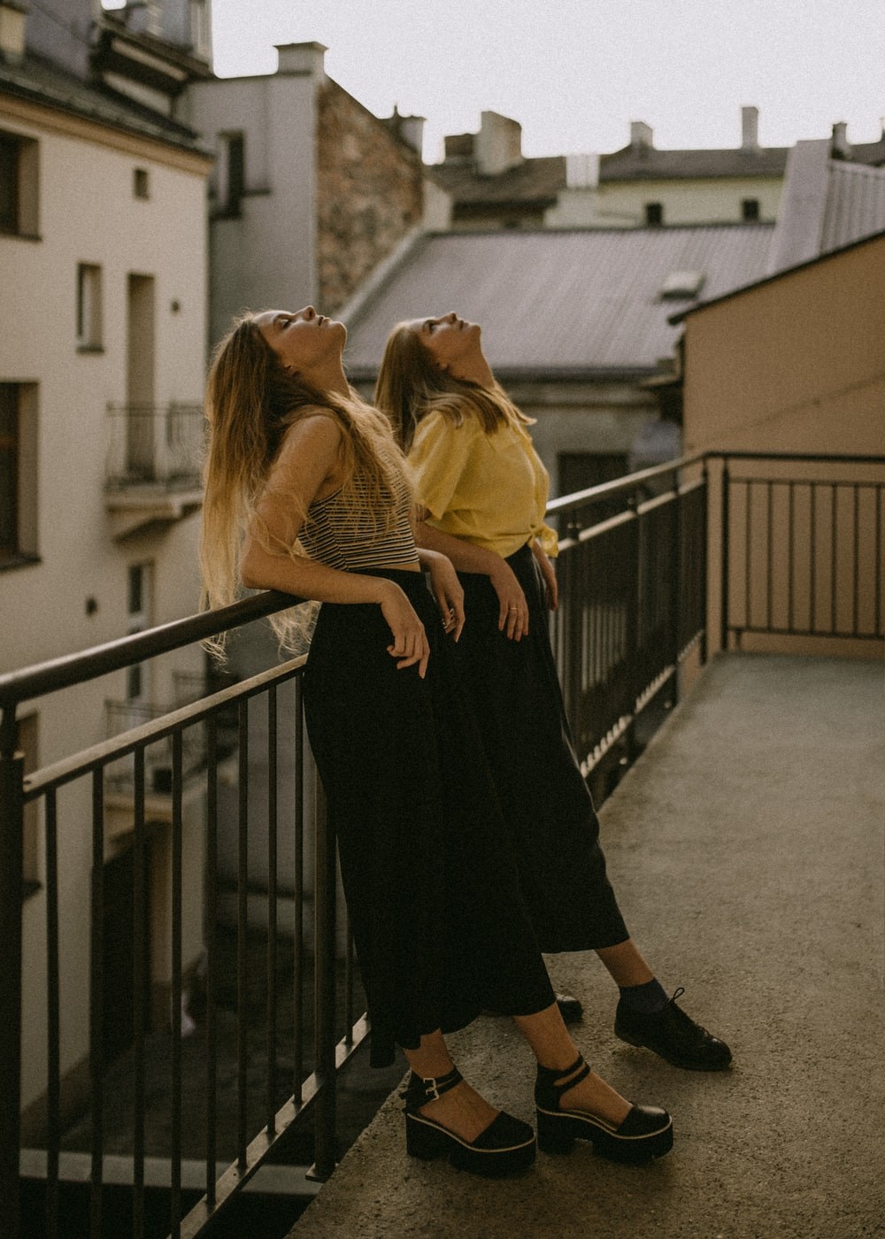 two women looking up white leaning on fence