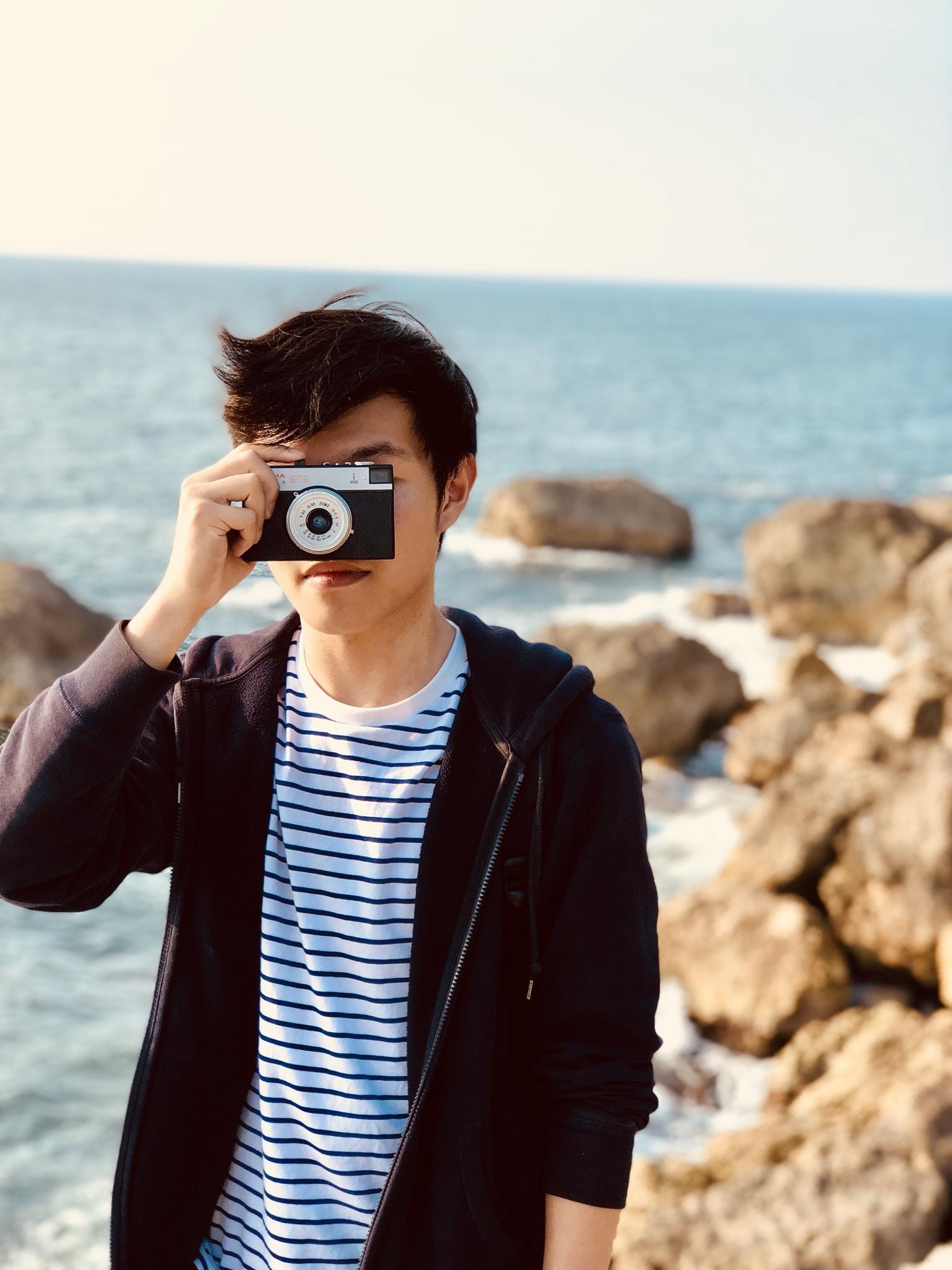 person taking photo using gray point-and-shoot camera near sea