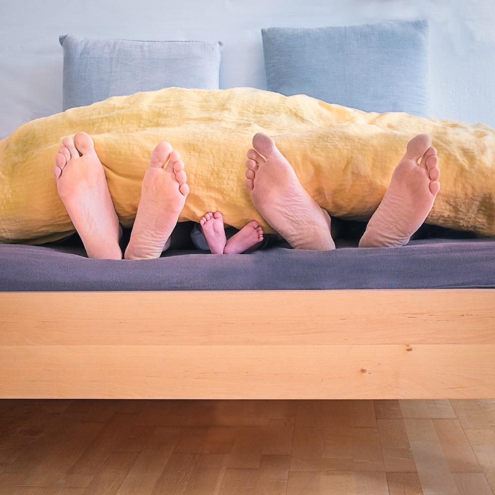 three people underneath yellow bed blanket