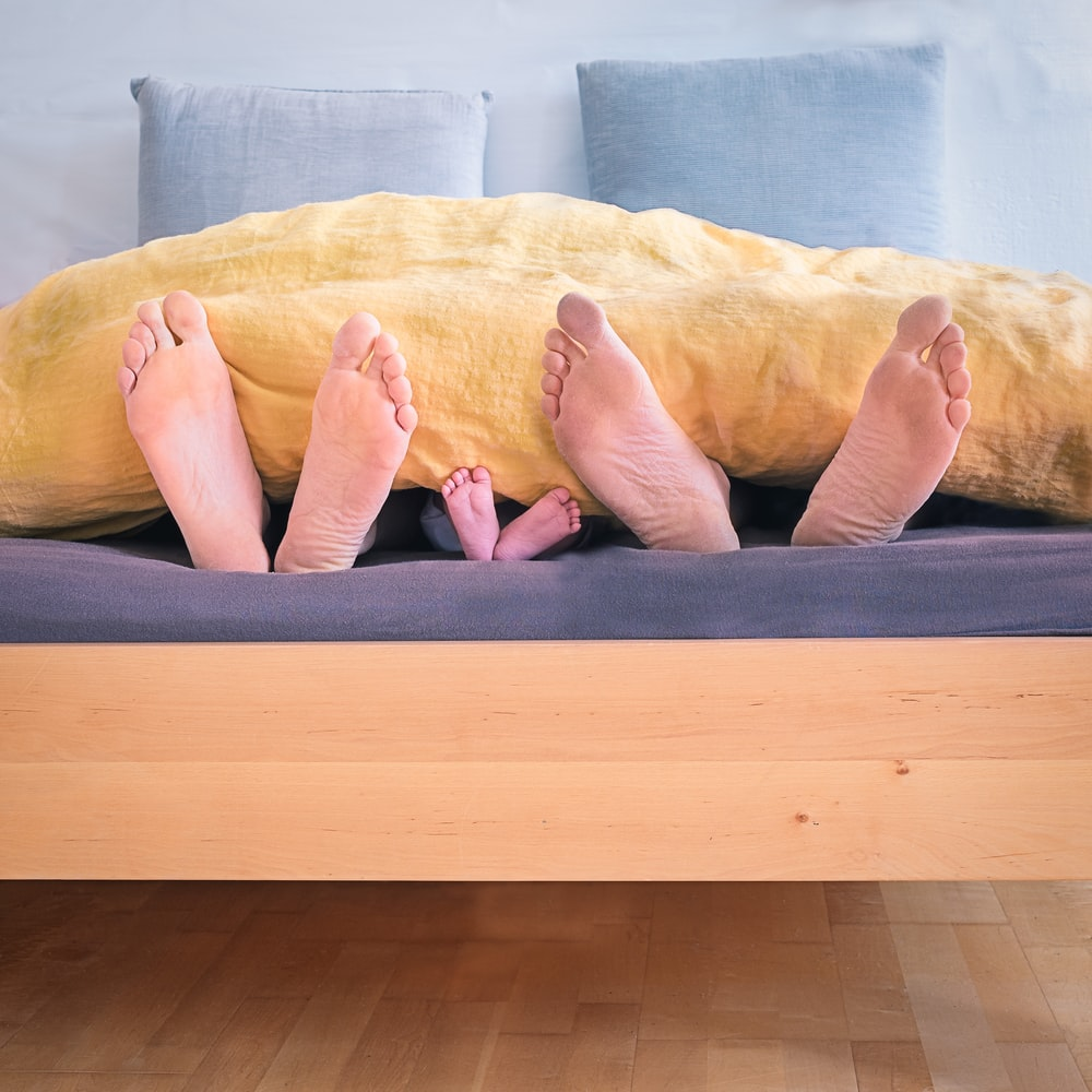 three people underneath yellow bed blanket