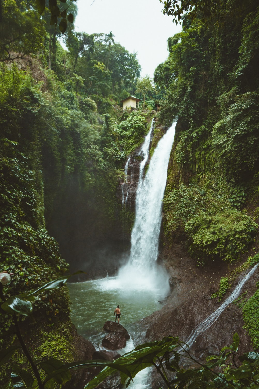 man standing on top of rock near waterfalls