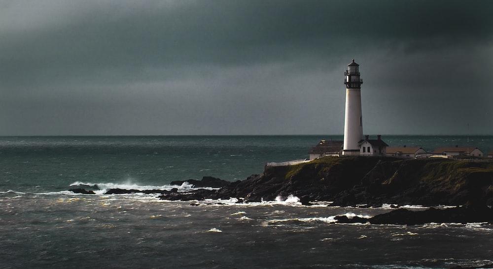 white lighthouse beside shore