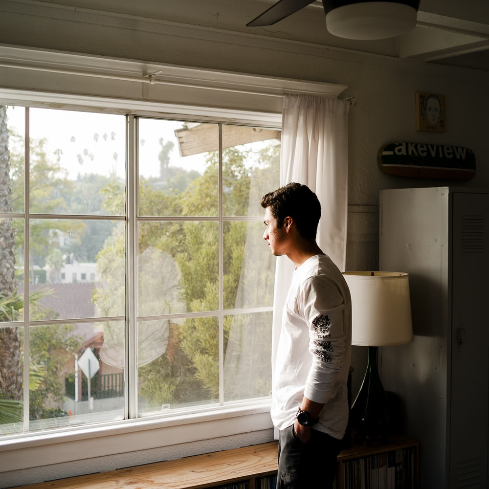 man wearing gray and black crew-neck shirt standing and looking out window
