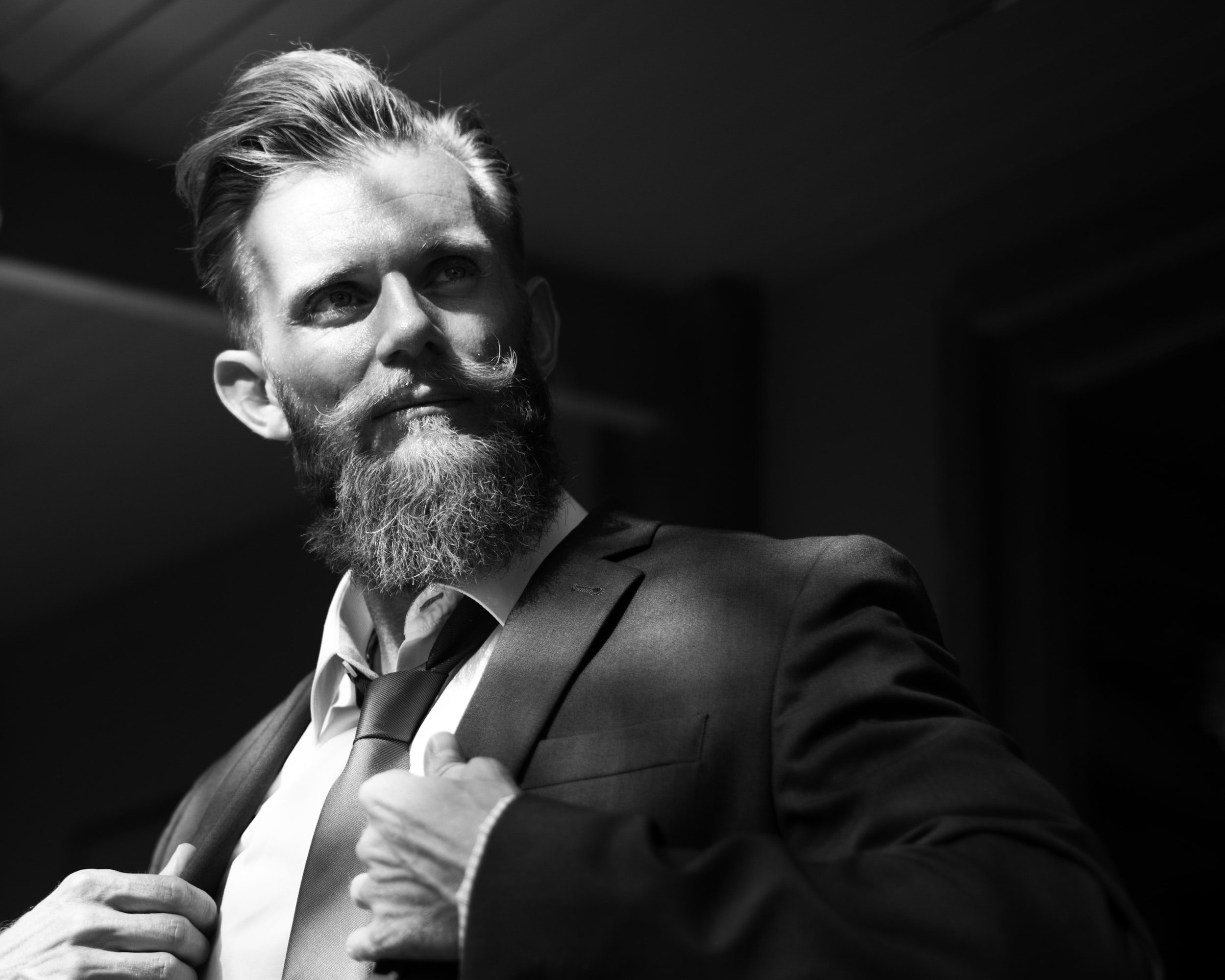 greyscale photo of man wearing notched lapel suit jacket