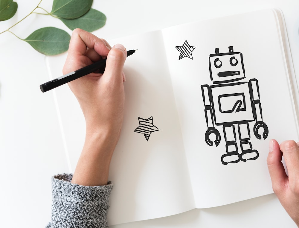 person drawing black robot with stars on paper