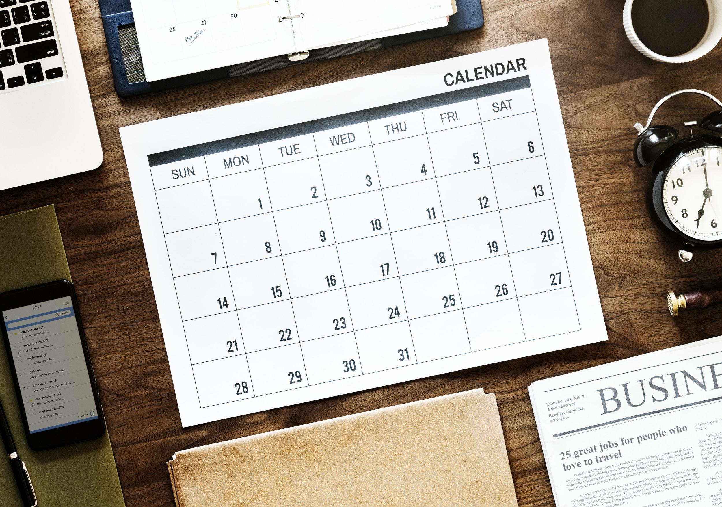 31-days calendar near round white analog alarm clock