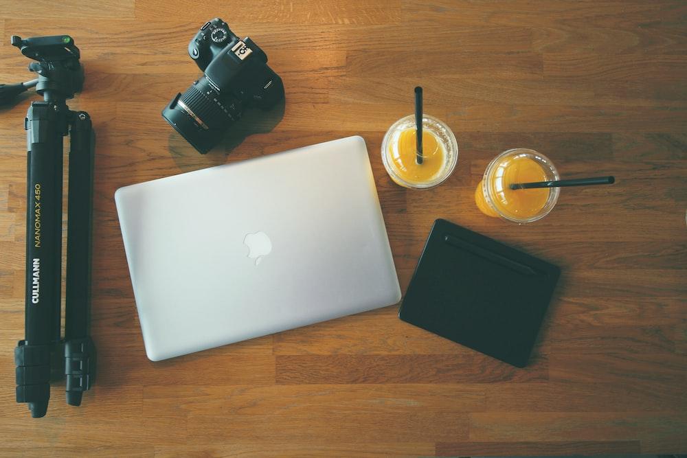 gray MacBook beside DSLR camera