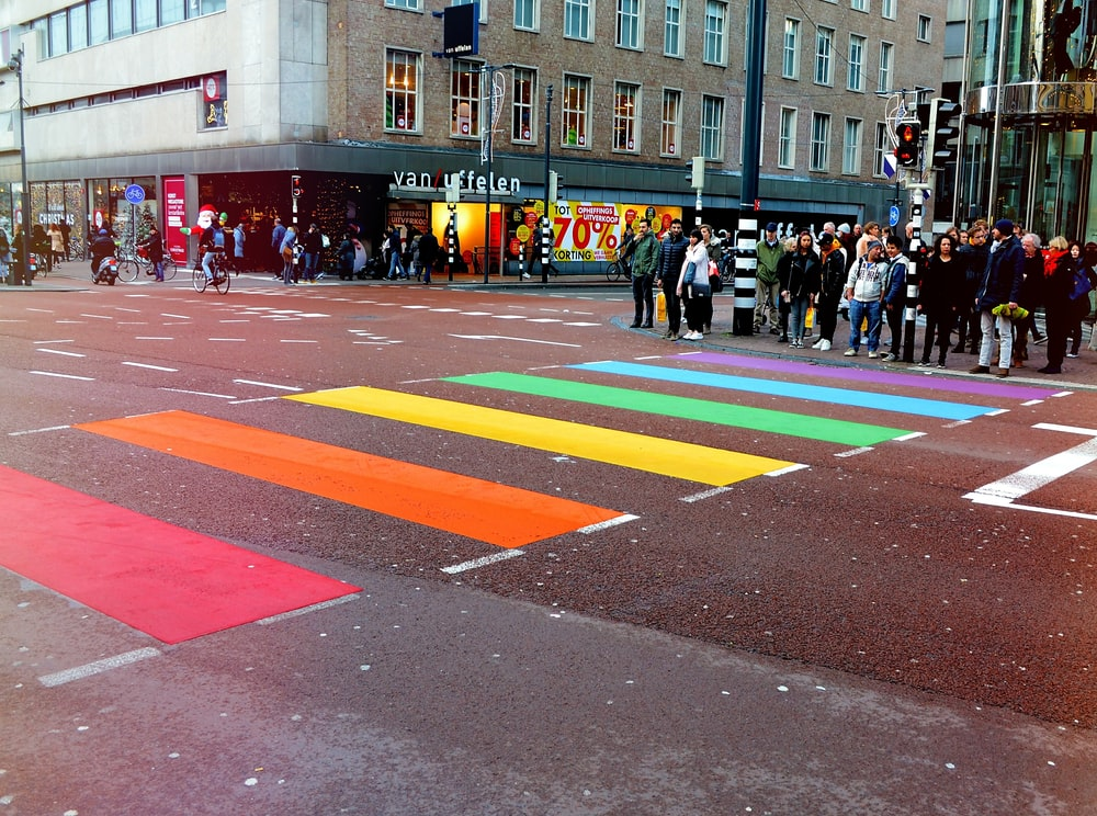 people standing on road in front of multicolored pedestrian line