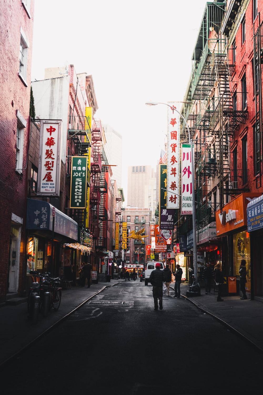photography of people walking on street between buildings