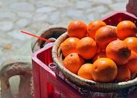 orange fruit in brown basket