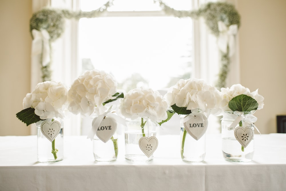 white flowers in glass jars