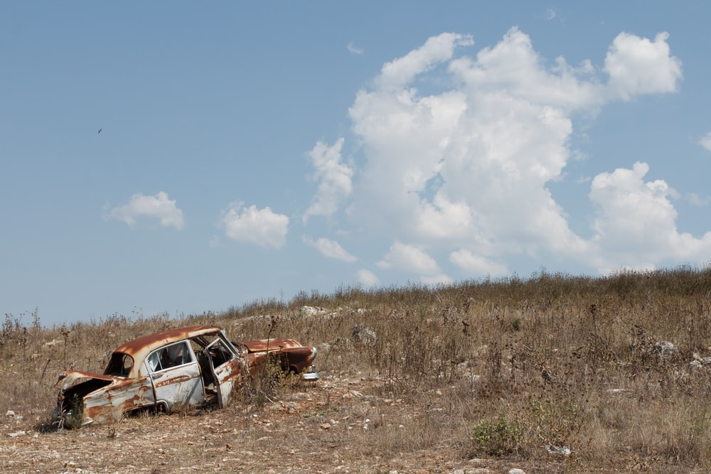 photo of wrecked sedan on brown grass field under clear blue sky