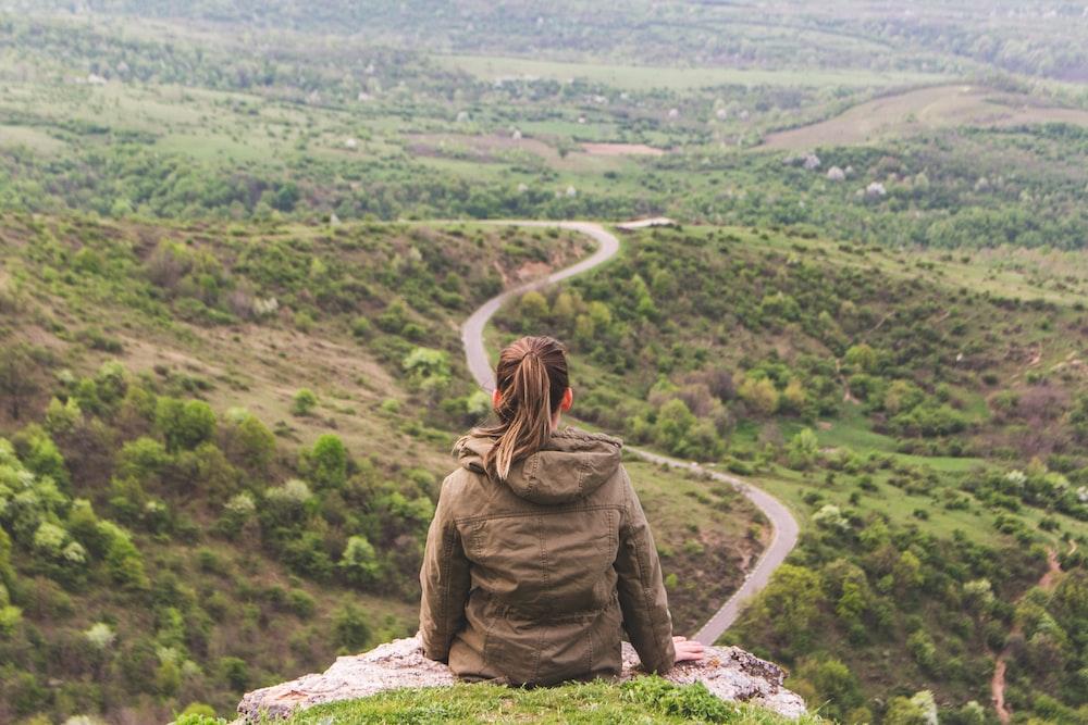 woman sitting on grey cliff