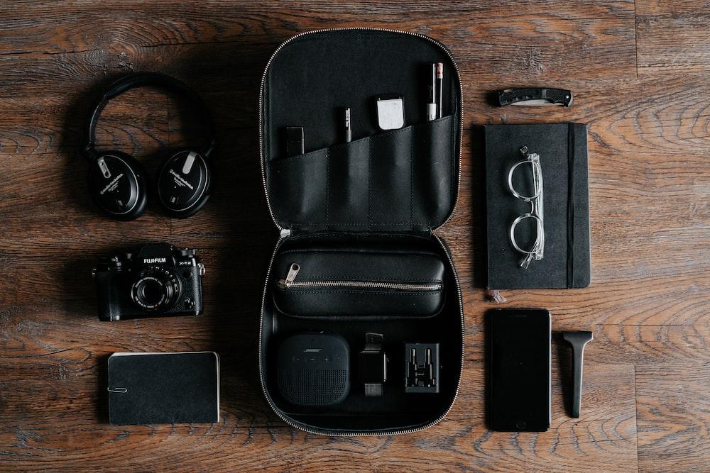 black headphones beside camera on top of wood