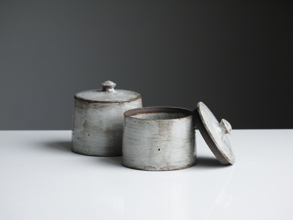 two grey containers on wooden table