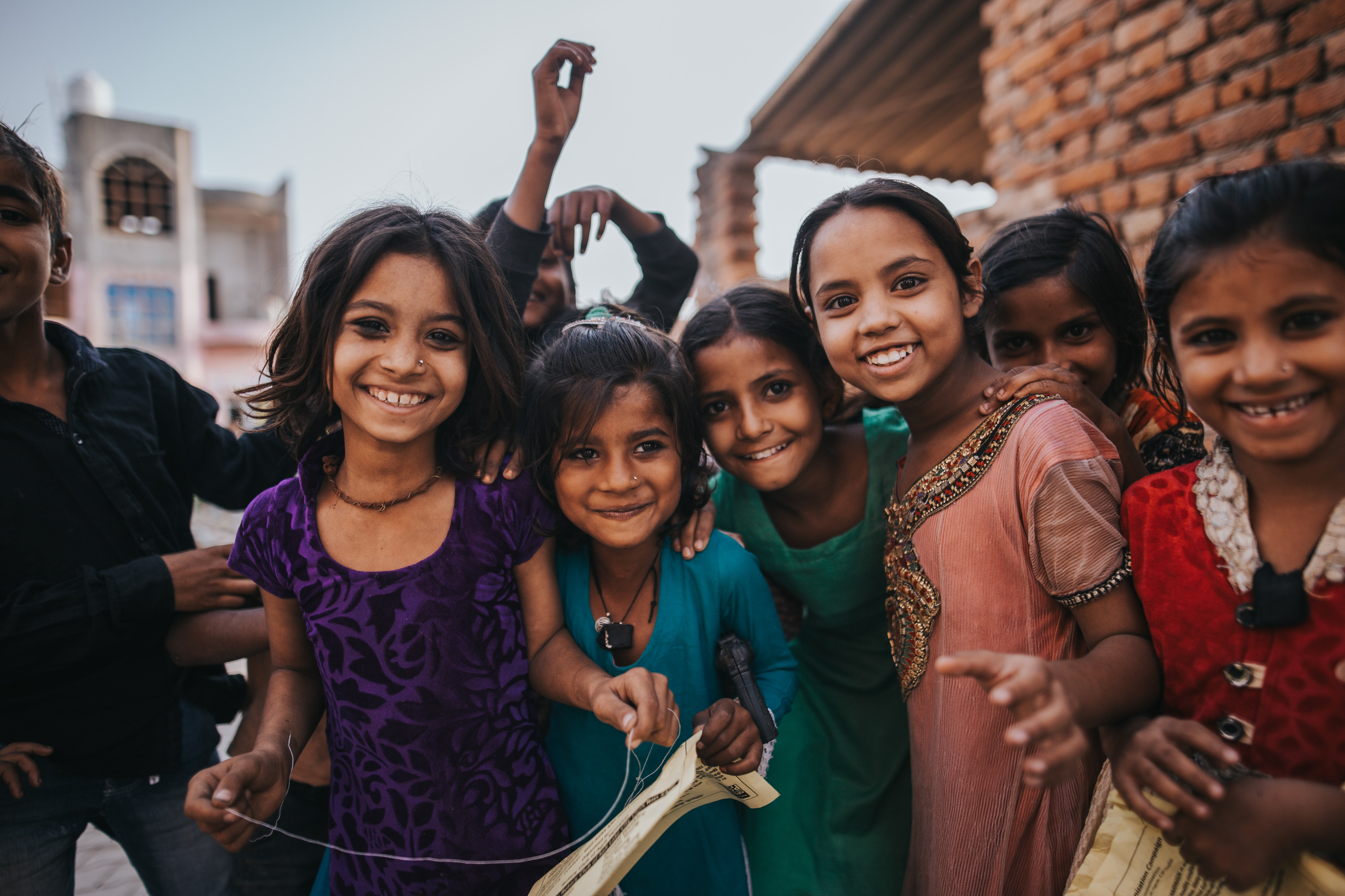 kids holding brown textile while smiling