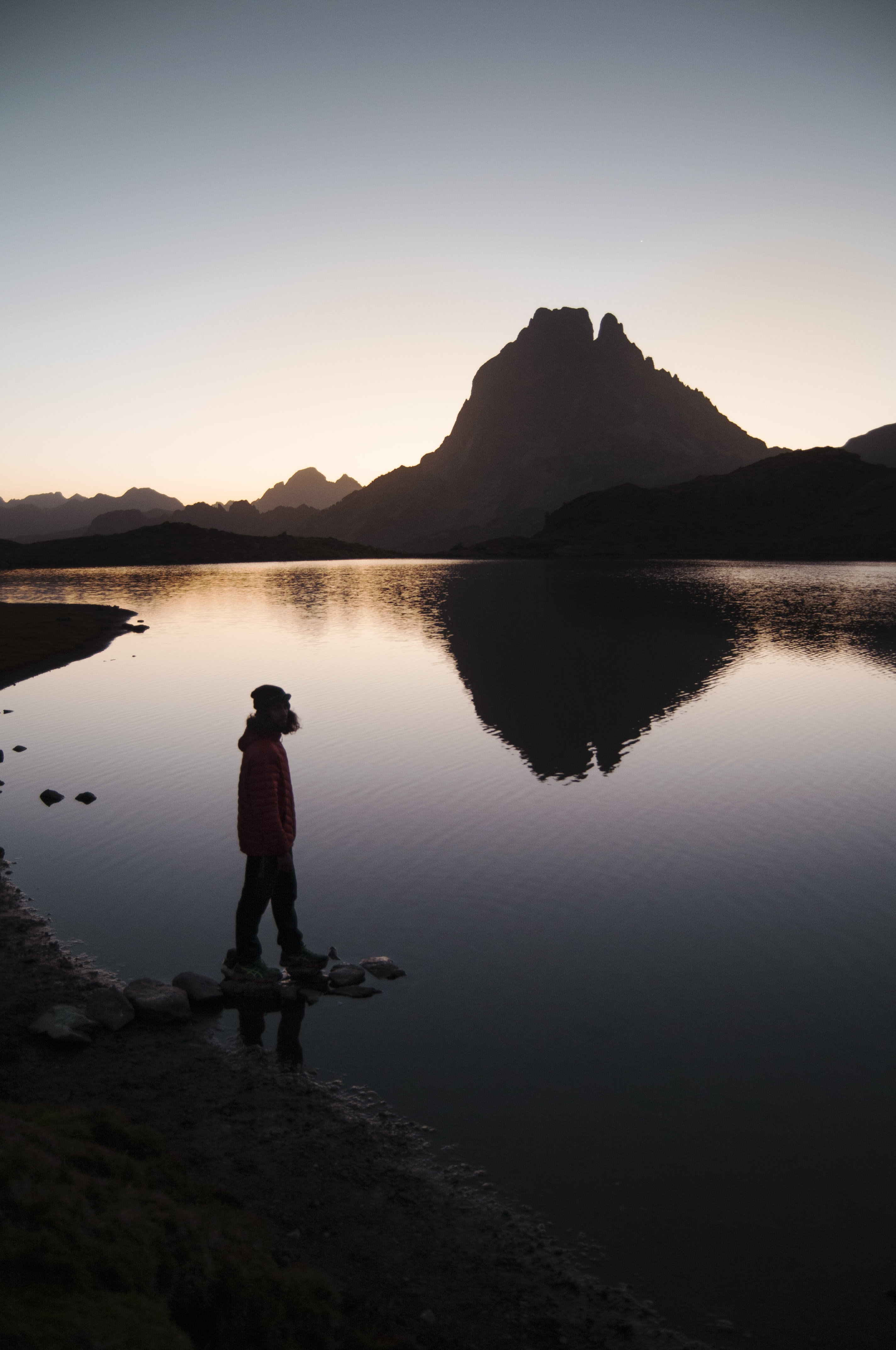 silhouette of person standing beside body of water near mountain during golden hour
