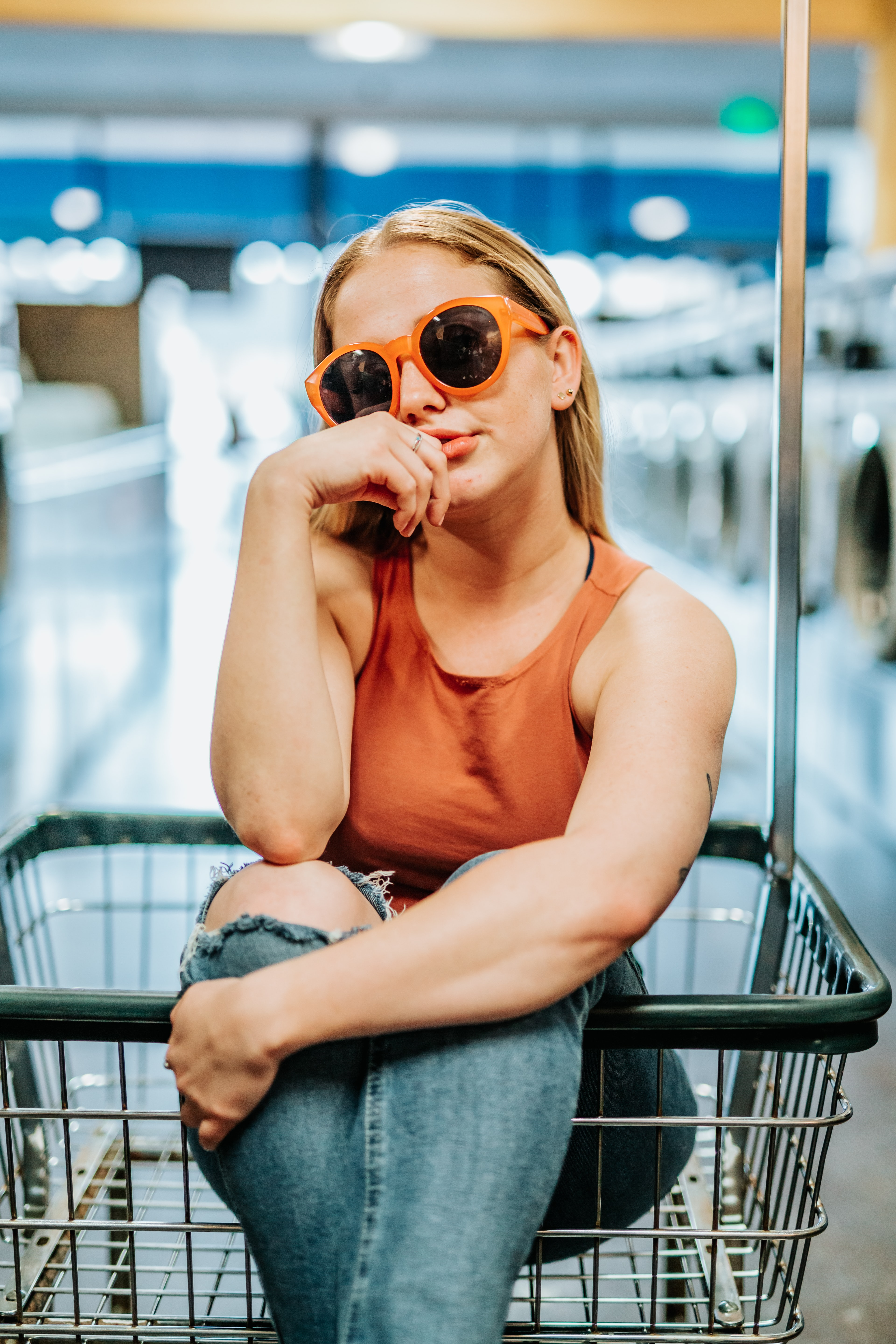 woman wearing brown tank top and jeans sitting in shopping cart