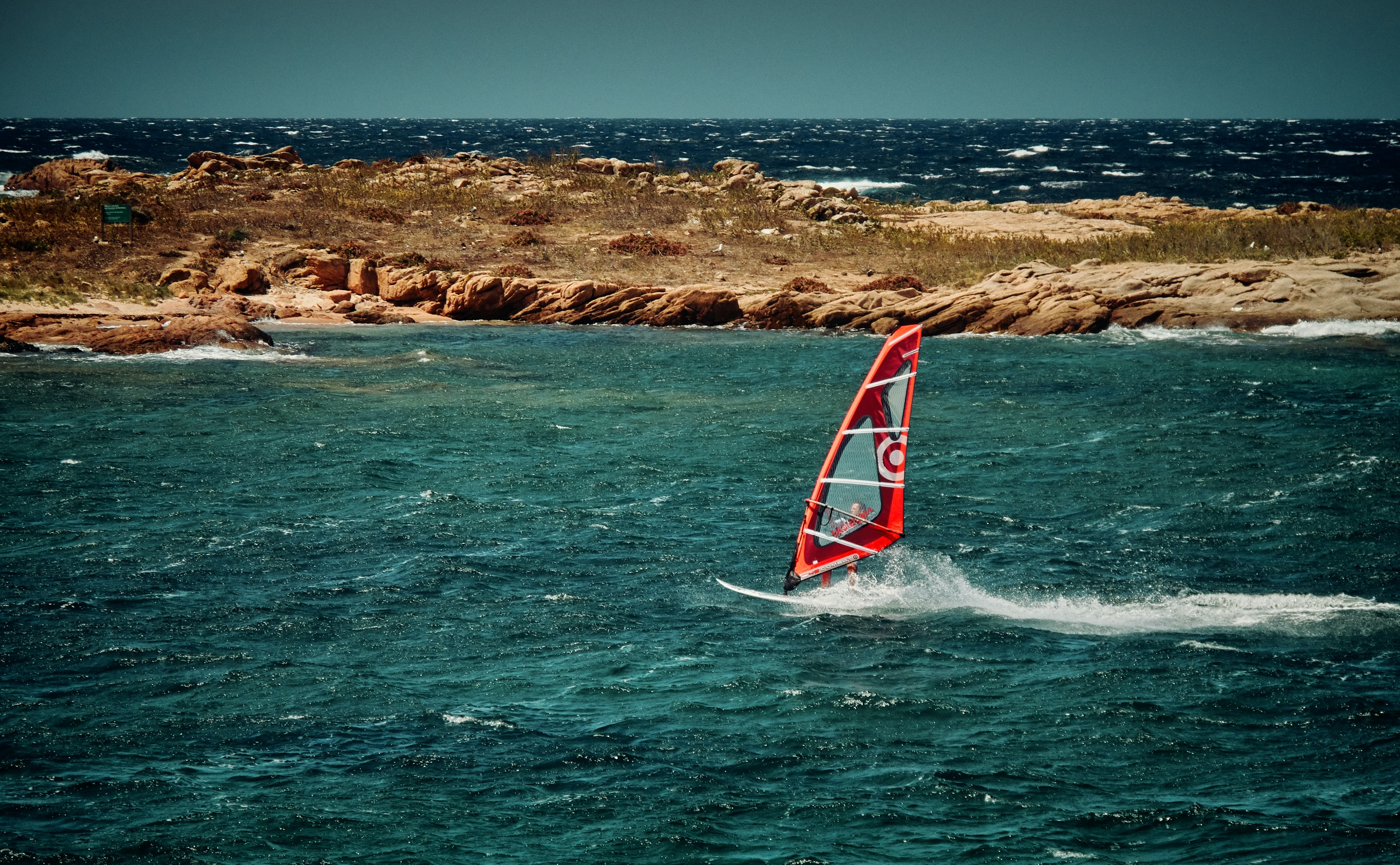 red sailing boat under blue sky