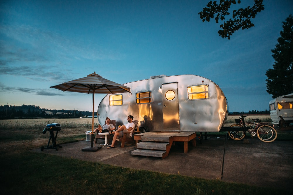 man and woman sitting in front of RV trailer