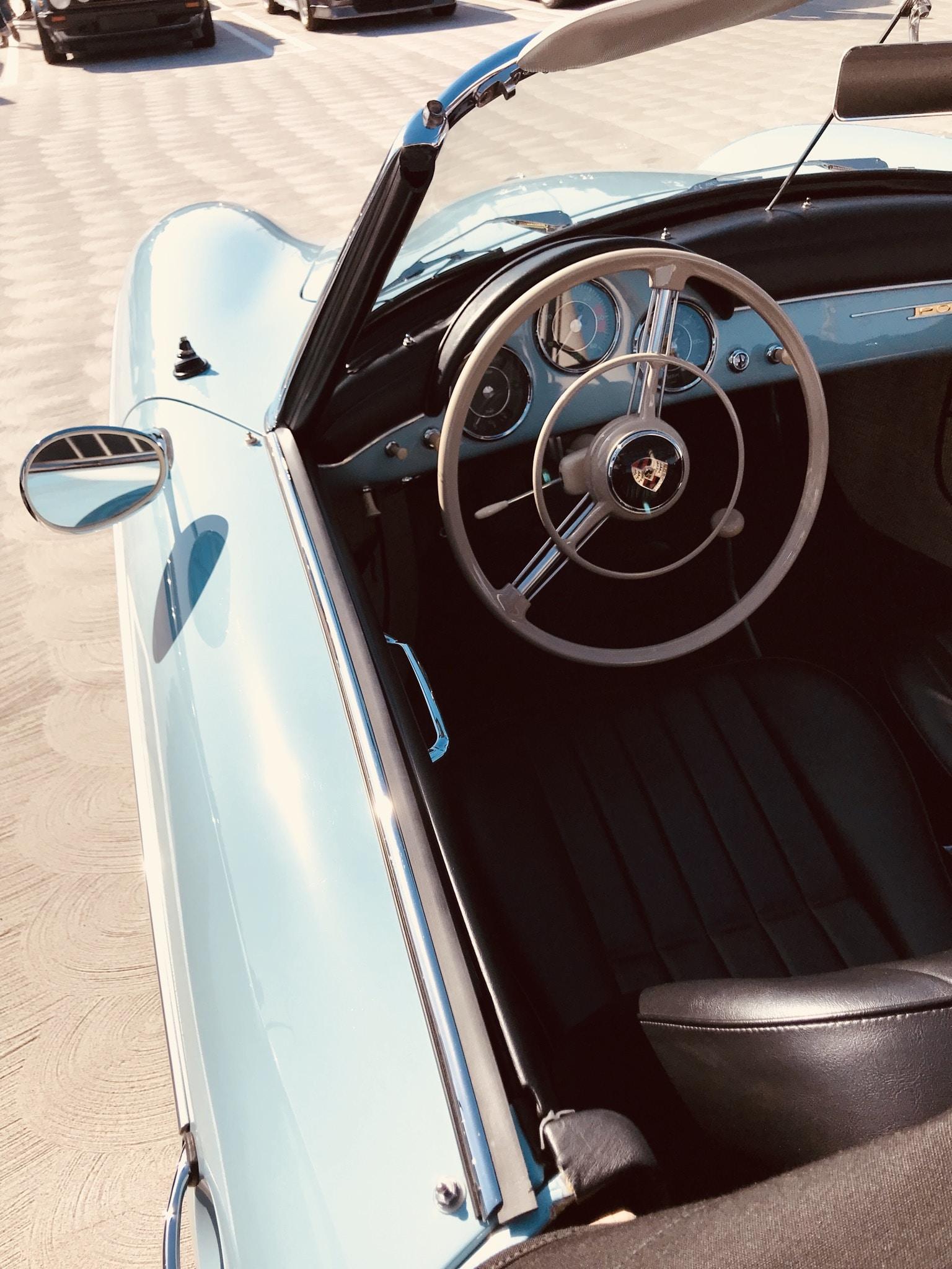 Porsche convertible parked on brown floor