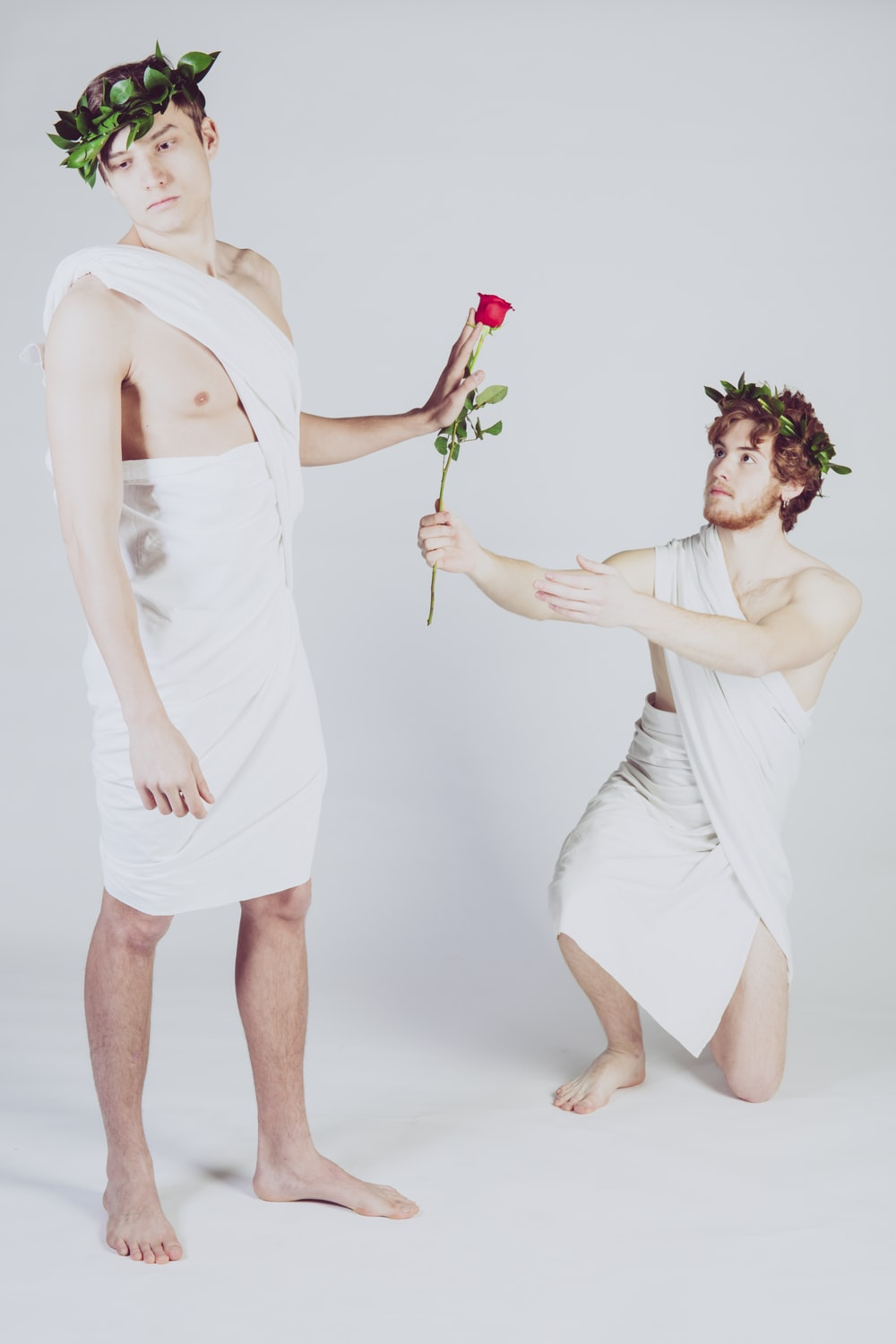 man giving rose to another man
