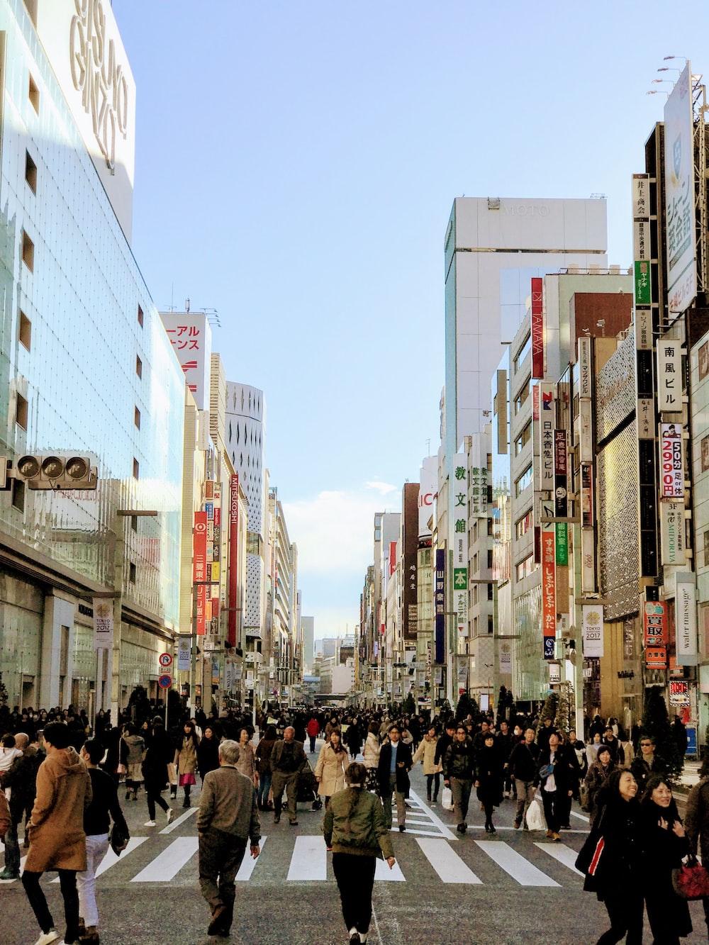 people walking on street in between buildings under blue sky