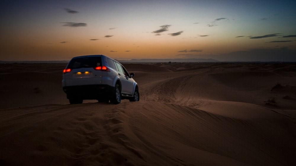 white SUV on desert during daytime