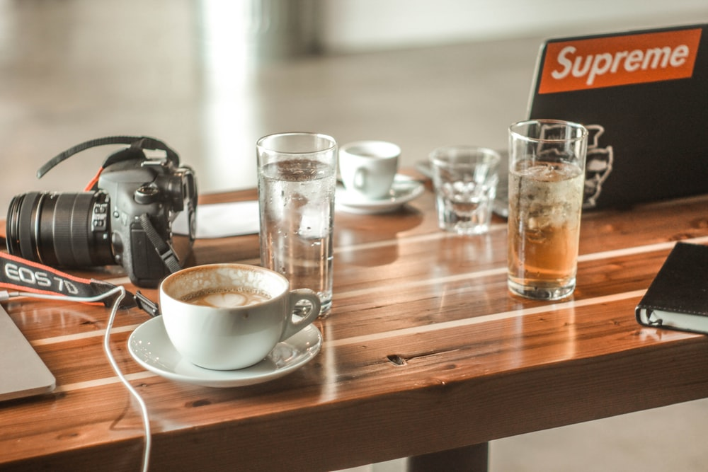 white teacup near Canon EOS 7D camera on brown wooden table