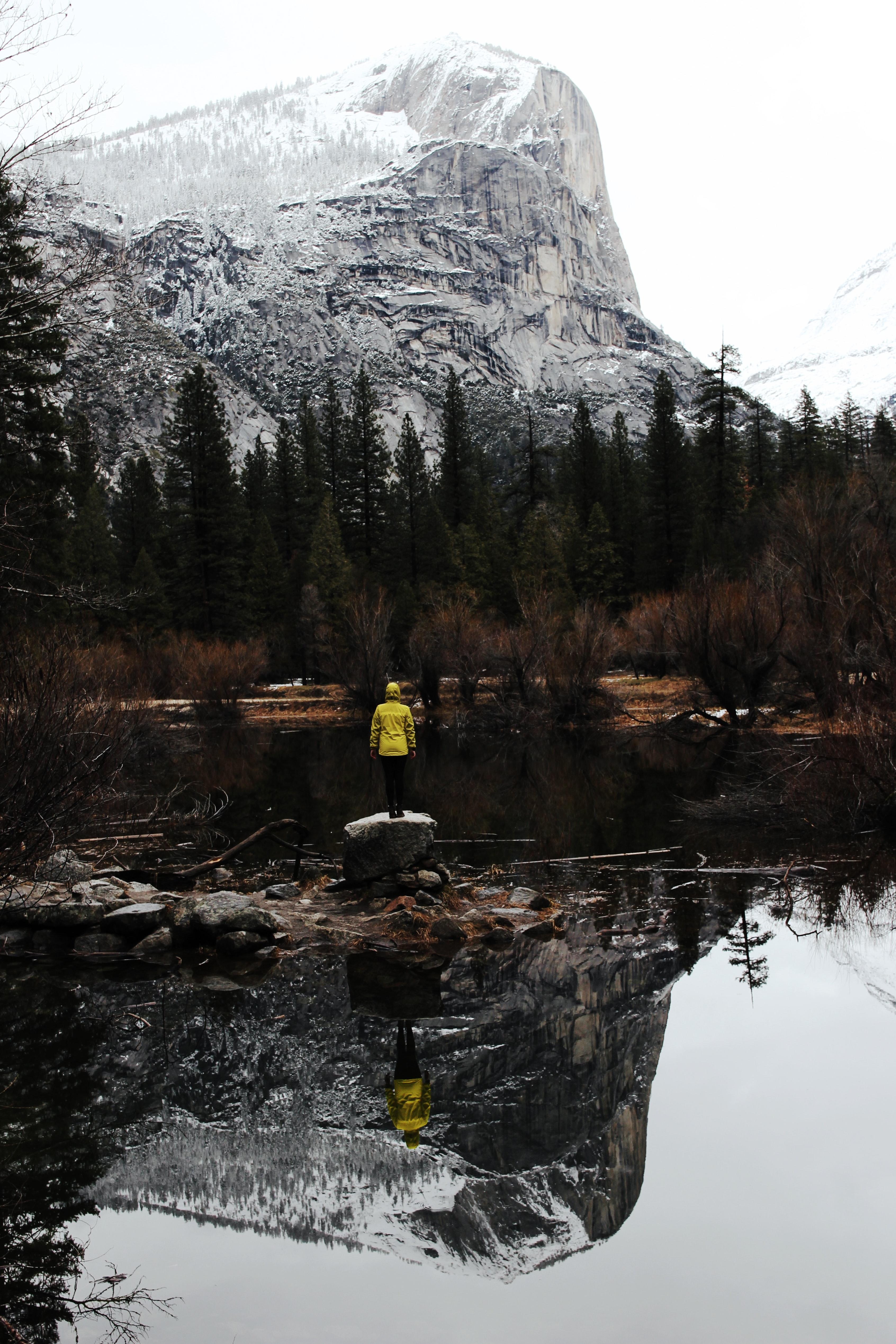 person wearing yellow hoodie standing on rock