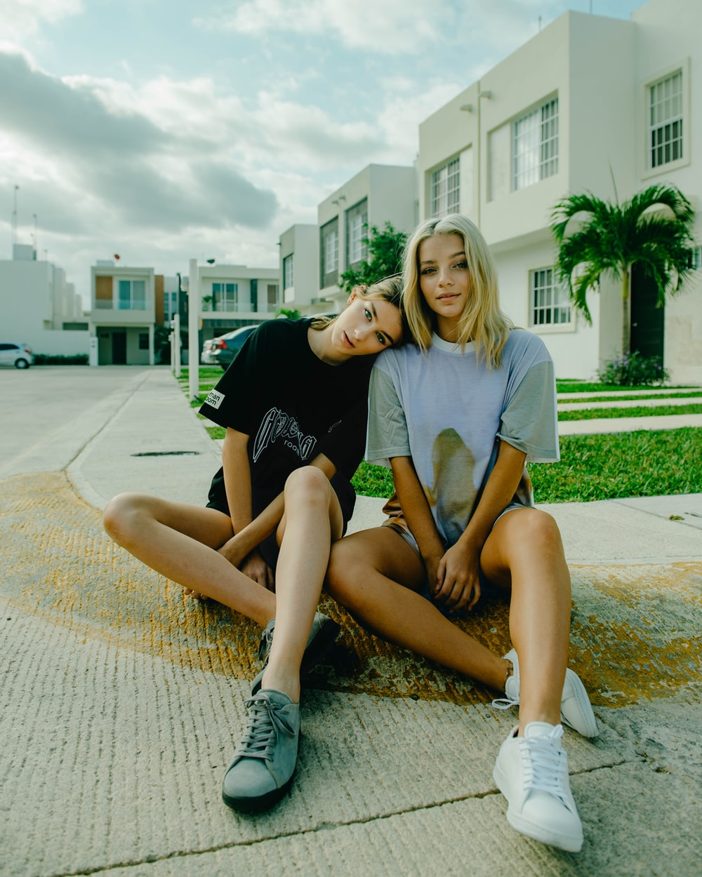two women sitting on pavement blocks