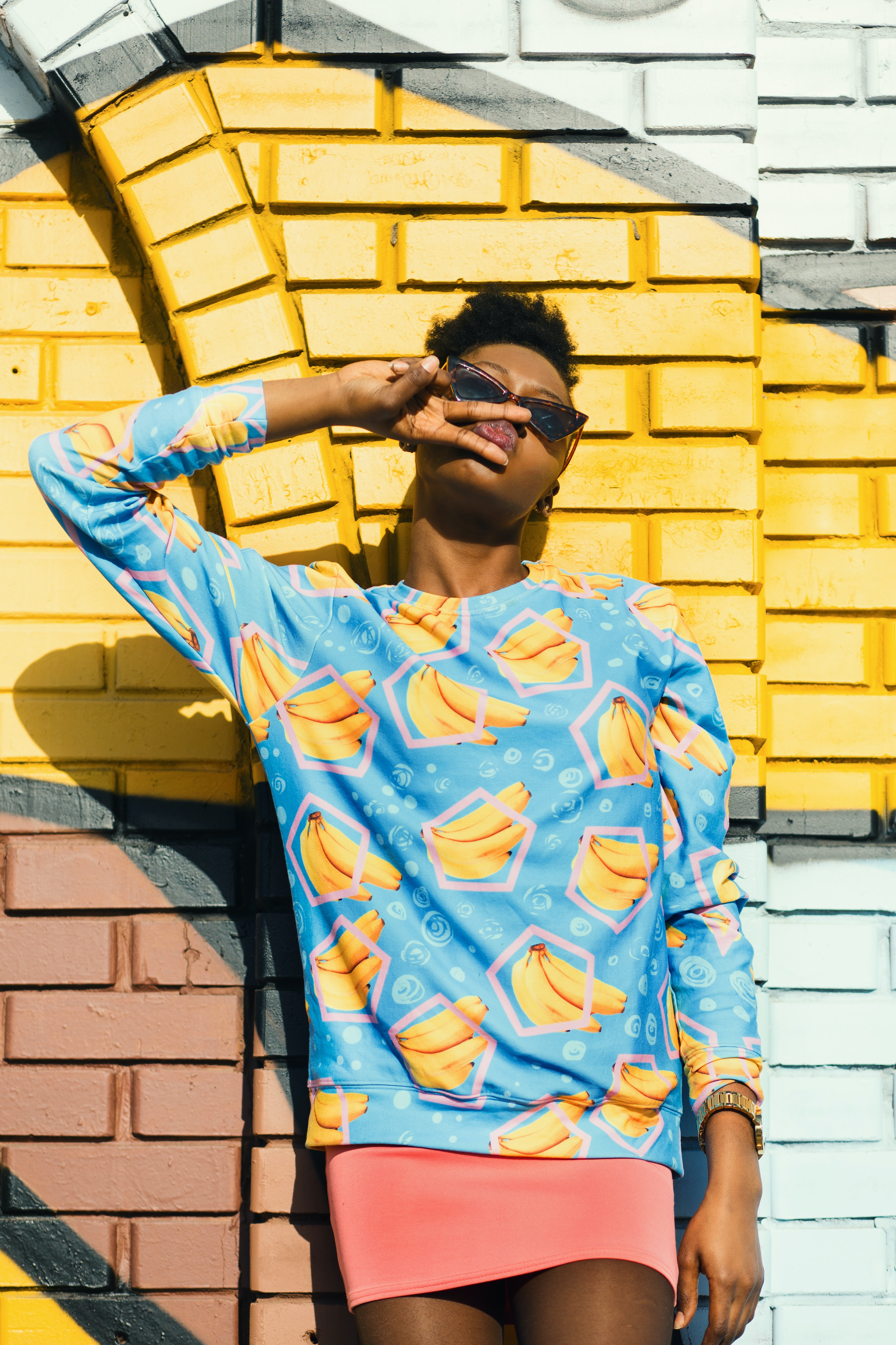 person leaning on wall wearing blue and yellow banana print long-sleeved shirt