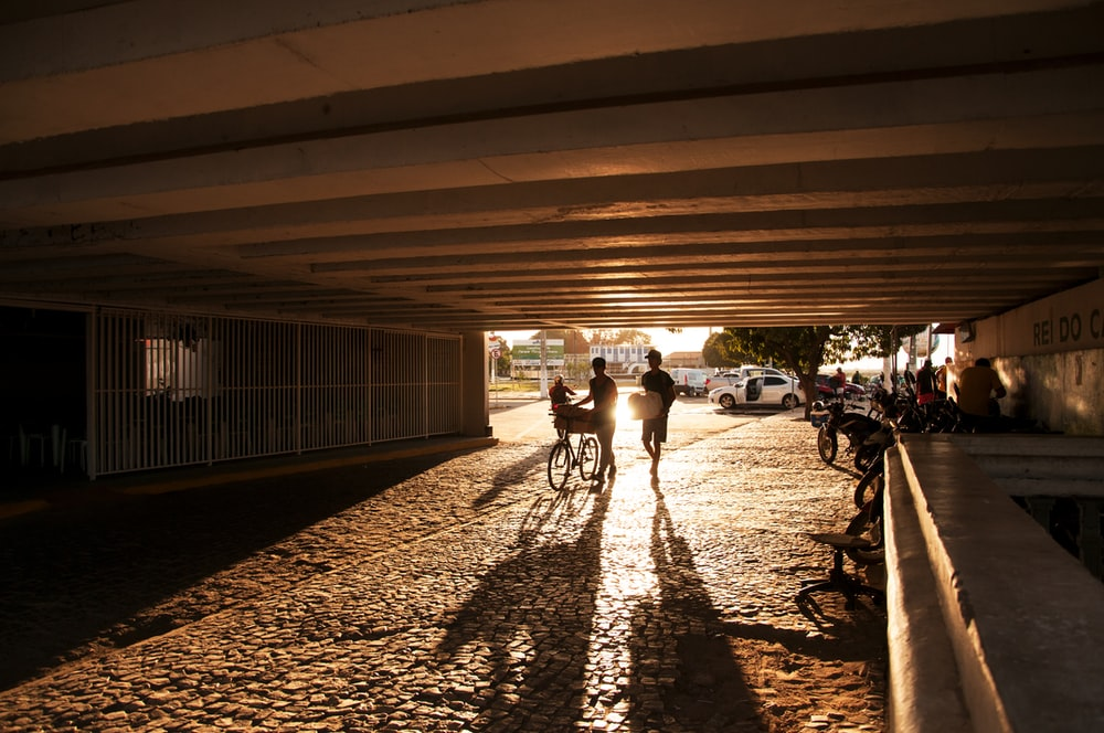 silhouette of two person walking under bridge