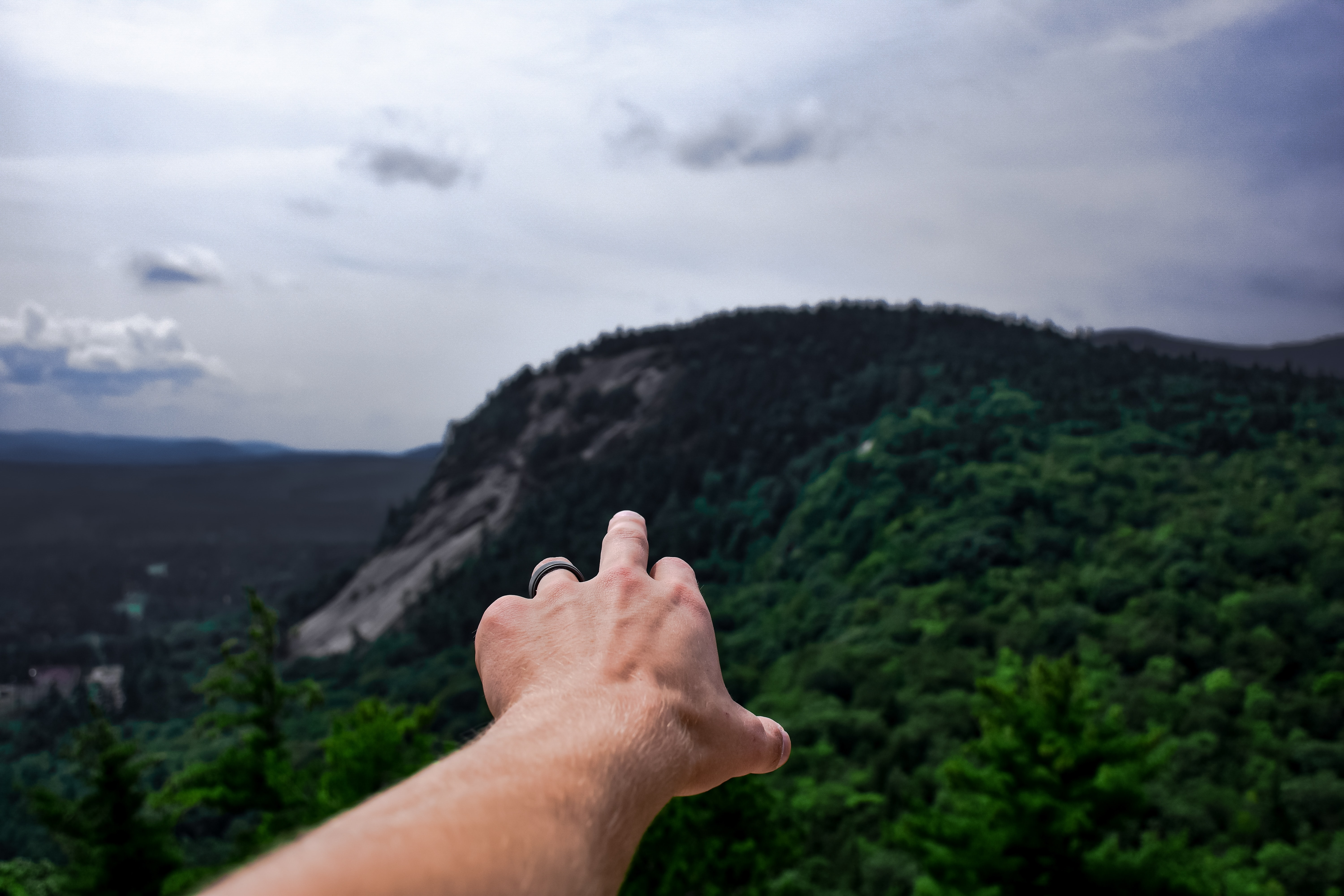 person pointing mountain with finger
